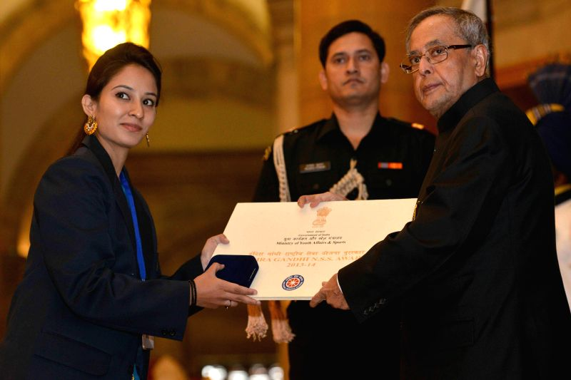 President Pranab Mukherjee with a recipient of the Indira Gandhi National Service Scheme Award 2013-14, at Rashtrapati Bhavan, in New Delhi on Nov 19, 2014. Also seen Union Minister of ... - Pranab Mukherjee