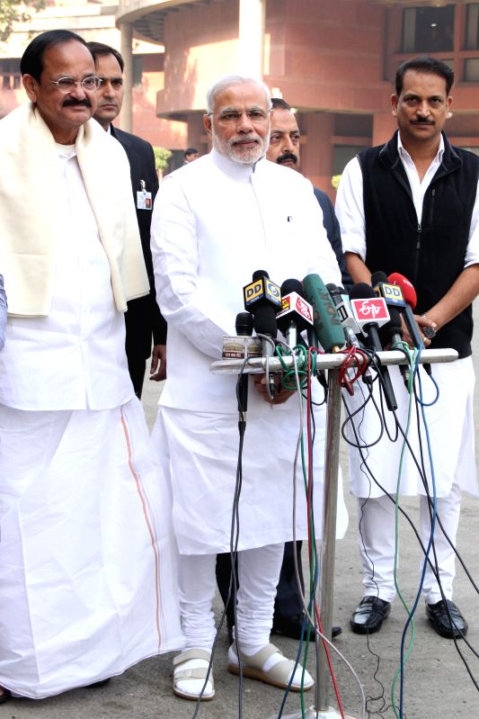Prime Minister Narendra Modi addresses press ahead of attending the first day of Parliament's winter session in New Delhi, on Nov 24, 2014. Also seen the Union Minister for Urban ... - Narendra Modi and M. Venkaiah Naidu