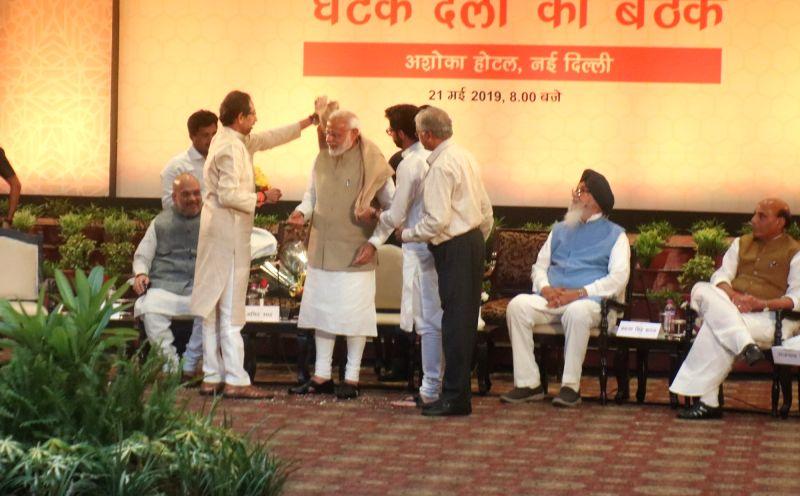 New Delhi: Prime Minister Narendra Modi being welcomed by Shiv Sena President Uddhav Thackeray along with his son and Yuva Sena chief Aaditya Thackeray during NDA dinner hosted by BJP chief Amit Shah at Ashoka Hotel in New Delhi on May 21, 2019. Also