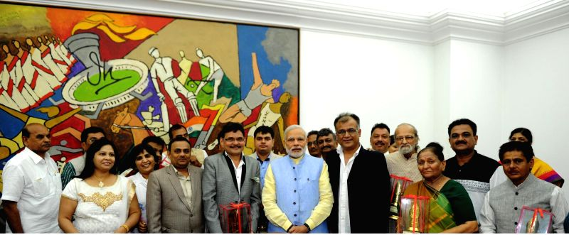 Prime Minister Narendra Modi hands over the annual Batukbhai Dikshit award of the Surat Shaher Patrakar Kalyan Nidhi to 13 Gujarati journalists, in New Delhi on March 18, 2015. - Narendra Modi