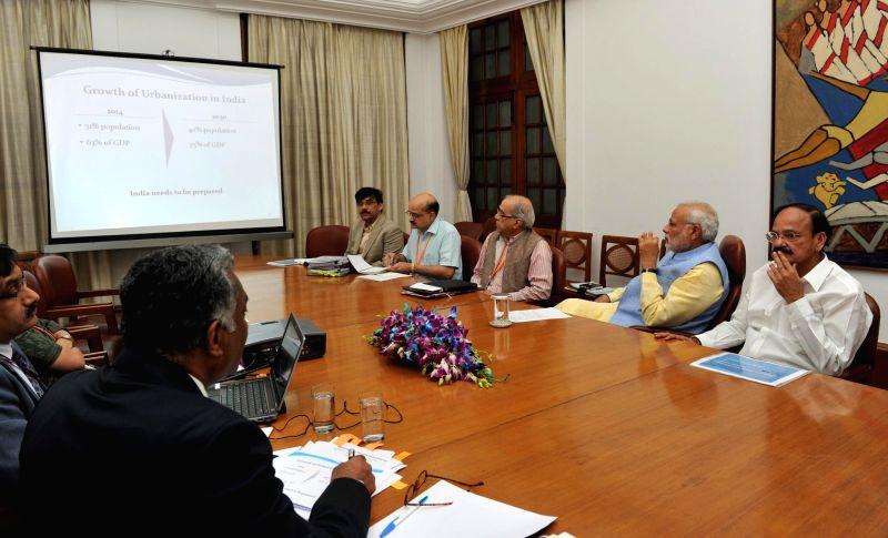 Prime Minister Narendra Modi reviews the progress of Urban Development Programmes, in New Delhi on March 18, 2015. Also seen the Union Minister for Urban Development, Housing and Urban ... - Narendra Modi and M. Venkaiah Naidu