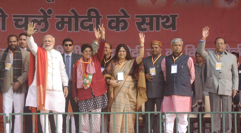 Prime Minister Narendra Modi with BJP leaders Kiran Bedi, Meenakshi Lekhi, Prabhat Jha and Vijay Kumar Malhotra during a Delhi Assembly Election rally in New Delhi on Feb. 4, 2015. - Narendra Modi, Kiran Bedi and Vijay Kumar Malhotra