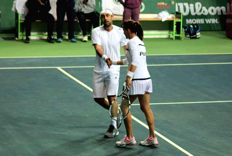 Pune players Marcos Baghdatis and Agnieszka Ranwanska celebrate after winning against Kevin Anderson and Jelena Jankovic of Delhi during Champions Tennis League (CTL) final match at R.K. ..