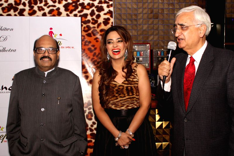 Rajya Sabha member Amar Singh (L) and Congress leader Salman Khurshid (R) during the launch of jewellery designer Chitwan Malhotra's (C) collection in New Delhi on Dec 9, 2014.