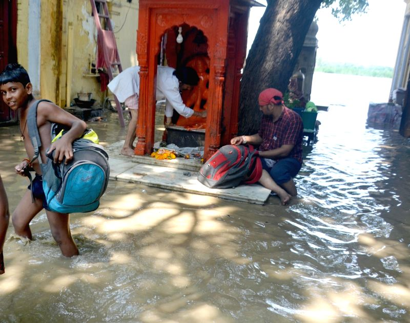 New Delhi: Residents of Yamuna Bazaar area struggle as waters from the Yamuna river left the locality inundated, in New Delhi on Aug 20, 2019. Close to 14,000 people living in low-lying areas along the Yamuna in Delhi were evacuated till Tuesday noon
