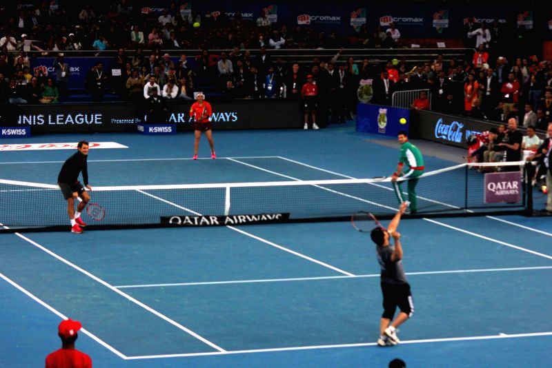 Roger Federer and Novak Djokovic lower the net after actor Aamir Khan hit a couple of double faults during IPTL matches at Indira Gandhi Indoor Arena in New Delhi, on Dec 8, 2014.