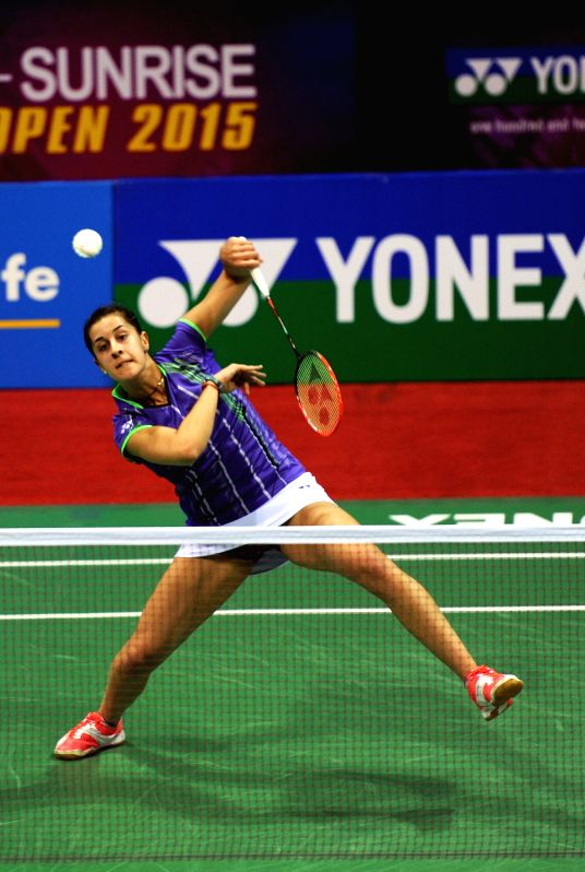 Spanish badminton player Carolina Marin returns a shot to Neha Pandit of India during the first round of the women's singles match of Yonex Sunrise Indian Open Badminton Championship in ...