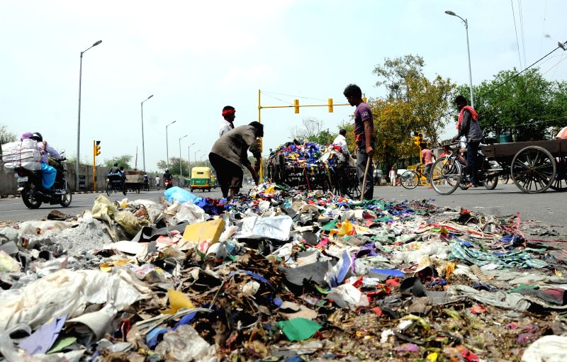 Striking MCD sanitation workers dump garbage on the road in Gandhi Nagar of New Delhi to press for their pending salaries on March 31, 2015.