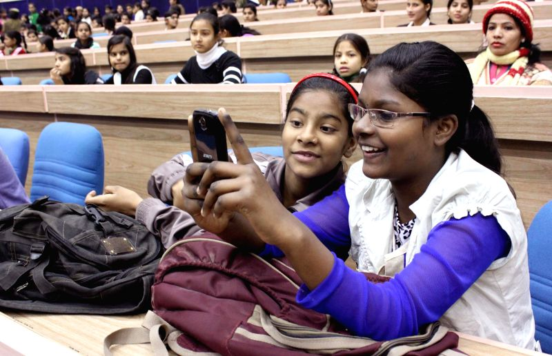 Students ​at the launch of Delhi Police's mobile app for public safety - `Himmat`, in New Delhi, on Jan 1, 2015.