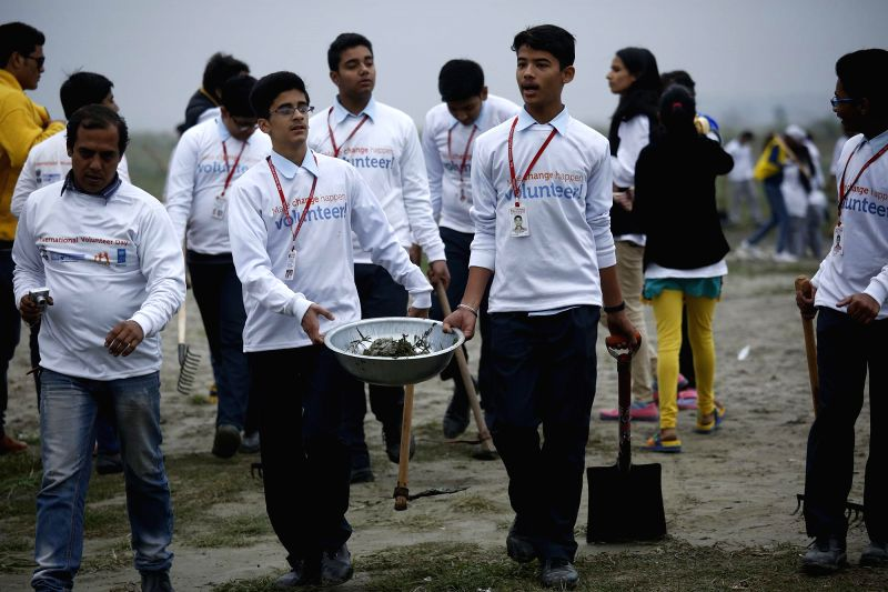 Students clean up the Yamuna river at Kudsi Ghat in New Delhi on Dec 14, 2014. The clean-up programme of the Yamuna river was organised by the Ministry of Youth Affairs and Sports, United .
