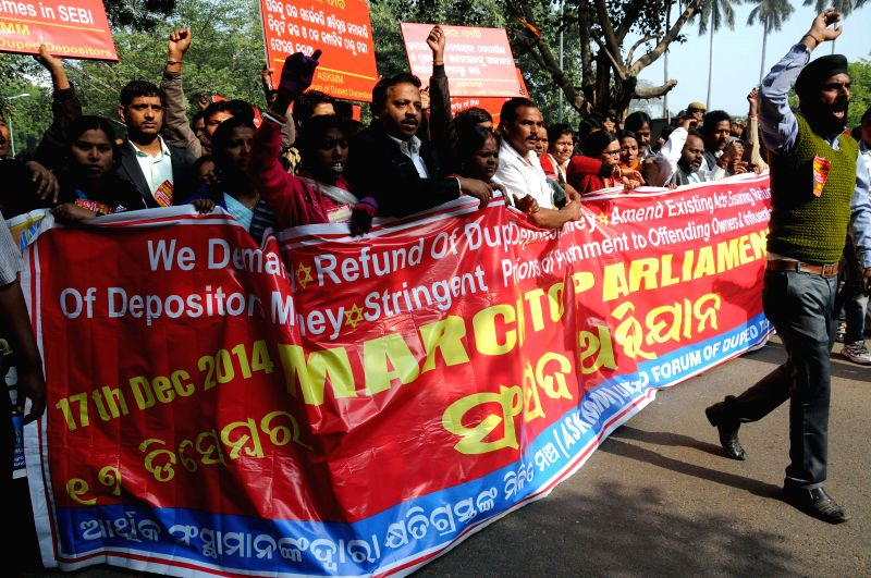 The members of United Forum of Duped Depositors march towards the Parliament to demand stringent action against the owners of chit fund groups, in New Delhi, on Dec 17, 2014.