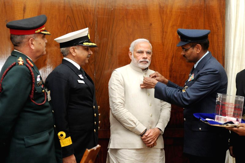 The Officers of the Kendriya Sainik Board pin a flag on the Prime Minister Narendra Modi, during the Armed Forces Flag Day, in New Delhi on Dec 4, 2014. - Narendra Modi