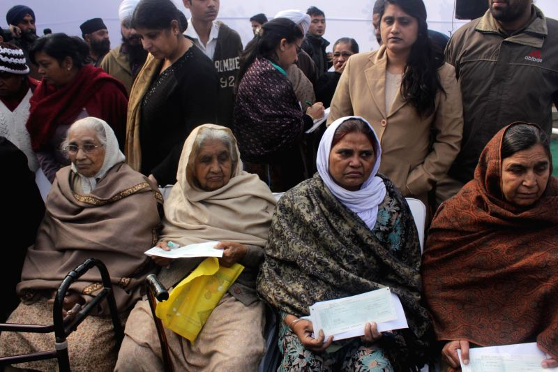 The recipients of enhanced compensation during a programme organised to distribute the compensations to the people affected by the 1984 anti-Sikh riots at Widow Colony Tilak Nagar, New ...