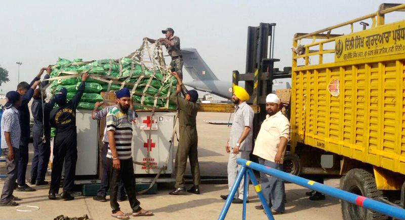 The sewadar's  of Delhi Sikh Gurdwara Management Committee hand over relief materials for Nepal quake victims to Air Force personnel at Palam airport, in New Delhi on April 27, 2015.