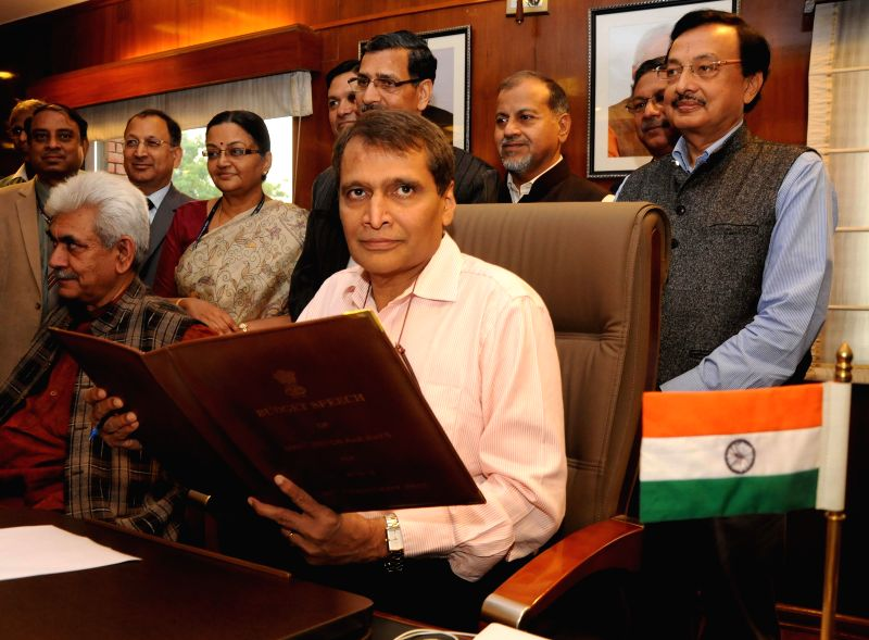 The Union Minister for Railways Suresh Prabhakar Prabhu gives finishing touches to the Railway Budget 2015-16, in New Delhi on Feb 25, 2015. Also seen the Union Minister of State for ... - Suresh Prabhakar Prabhu and Manoj Sinha