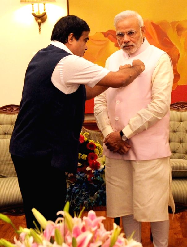 The Union Minister for Road Transport and Highways and Shipping, Nitin Gadkari pins a flag on the Prime Minister Narendra Modi on the National Maritime Day, in New Delhi on March 30, 2015. - Narendra Modi