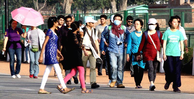 Tourists wear masks as a precautionary measure against swine flu in New Delhi, on Feb 25, 2015.
