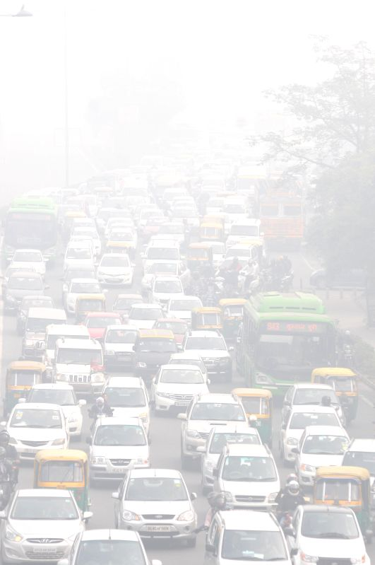 Traffic slows down on Vikas Marg due to dense fog cover in New Delhi, on Dec 22, 2014.