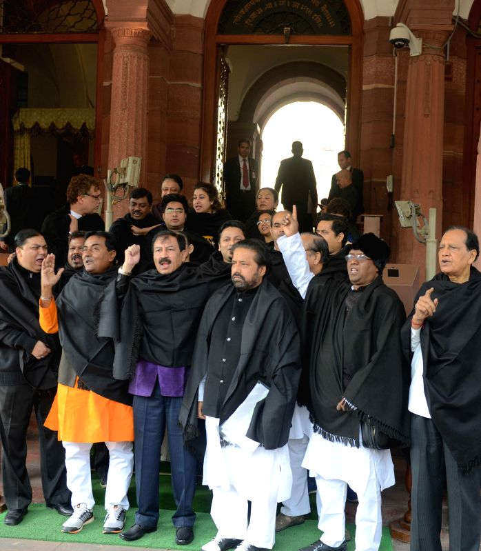 Trinamool Congress parliamentarians draped in black shawls stage a demonstration to press for bringing back the black money stashed abroad, at the Parliament house in New Delhi on Nov 27, .