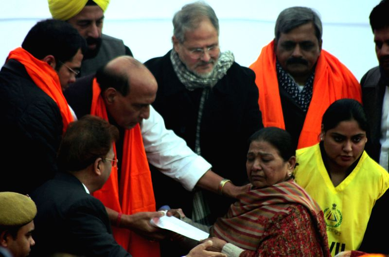 Union Home Minister Rajnath Singh distributes enhanced compensations to people affected by the 1984 anti-Sikh riots at Widow Colony Tilak Nagar, New Delhi  on Dec 26, 2014.