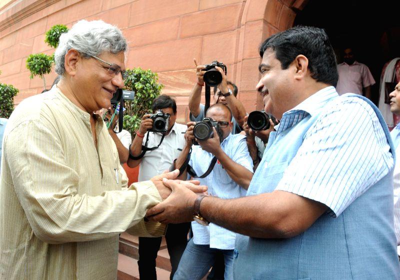 Union Minister Nitin Gadkari congratulates the newly elected CPI-M General Secretary Sitaram Yechury at the Parliament in New Delhi, on April 21, 2015.
