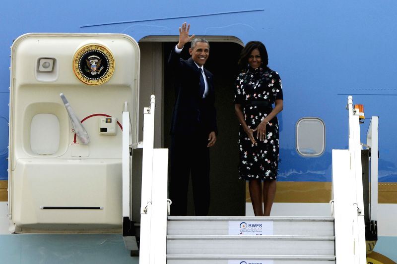 US President Barack Obama and First Lady Michelle Obama gesture as they board Air Force One prior to departing from Air Force Station Palam in New Delhi on Jan. 27, 2014.