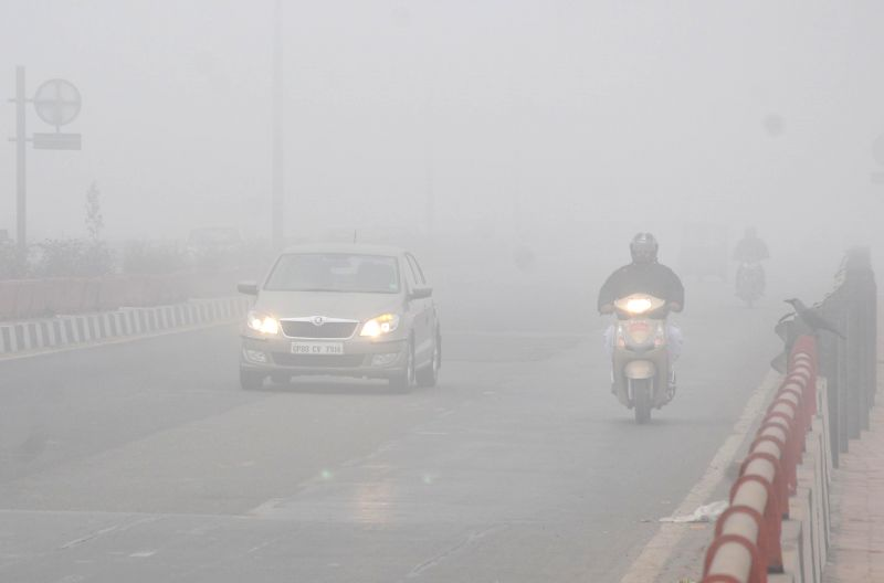 Vehicles ply with their headlights switched-on, as a blanket of dense fog covers New Delhi.