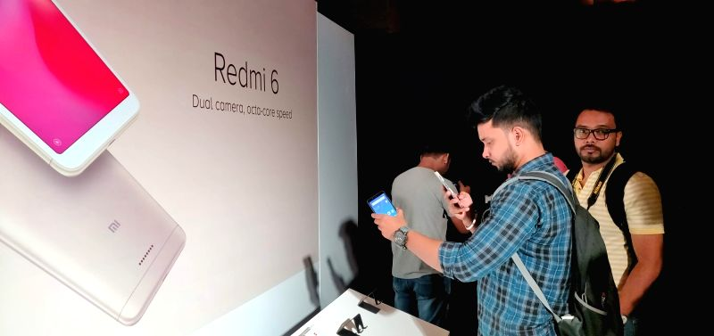 New Delhi: Visitors check out the features of newly launched Xiaomi Redmi 6 series smartphone, in New Delhi, on Sept 5, 2018. Also launched Xiaomi Redmi 6A and Redmi 6 Pro smartphone.