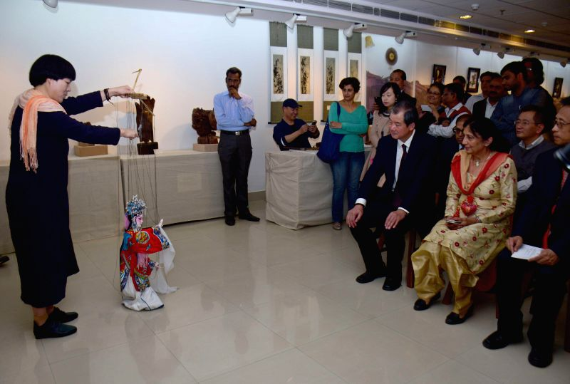 Visitors during a puppet show organised during `Zhejiang Cultural Exhibition`  at Arts and Crafts Society in New Delhi, on Nov 21, 2014. The exhibition is being organised by FICCI in ...