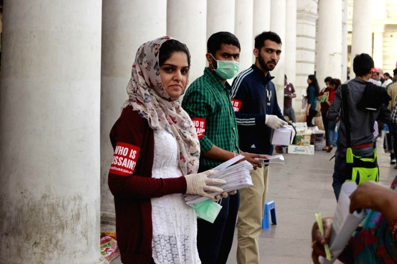 Volunteers of a social organisation distribute masks in the weak of outbreak of swine flu at Connaught Place in New Delhi, on Feb 23, 2015.