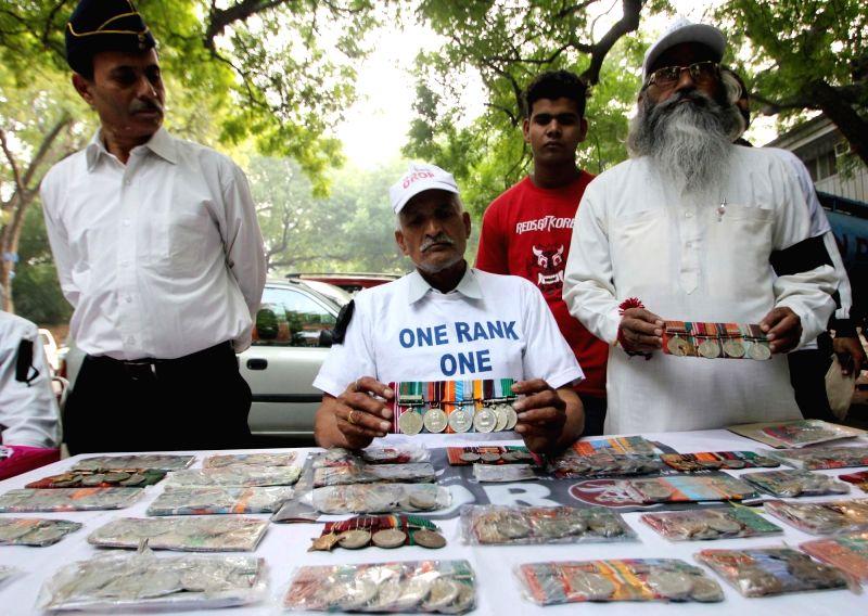 :â€‹New Delhi: War veterans return their medals to press for faster implementation of OROP at Jantar Mantar in New Delhi on Nov 10, 2015. (Photo: IANS).