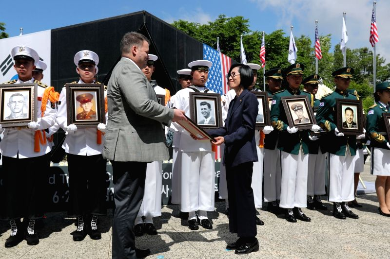 New Patriots and Veterans Affairs Minister Pee Woo-jin (R) presents a portrait of an American soldier missing in the 1950-53 Korean War to his bereaved family member, as they take part in a memorial ... - Pee Woo
