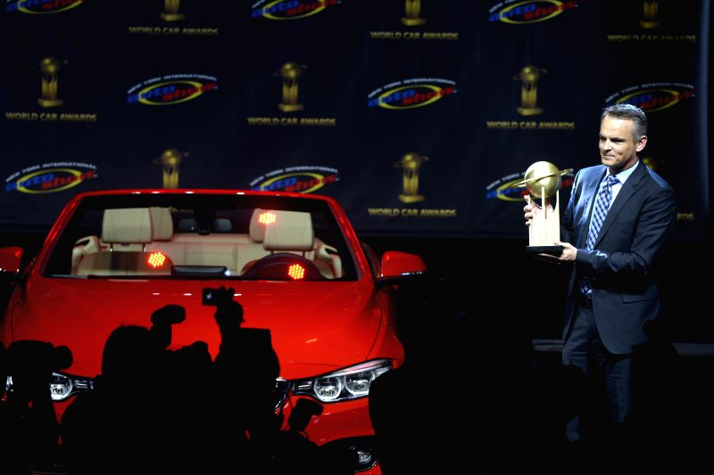 Detlev von Platen, president and CEO of Porsche Cars North America, poses as he accepts the award for the World Performance Car of the Year for the Porsche 911 at