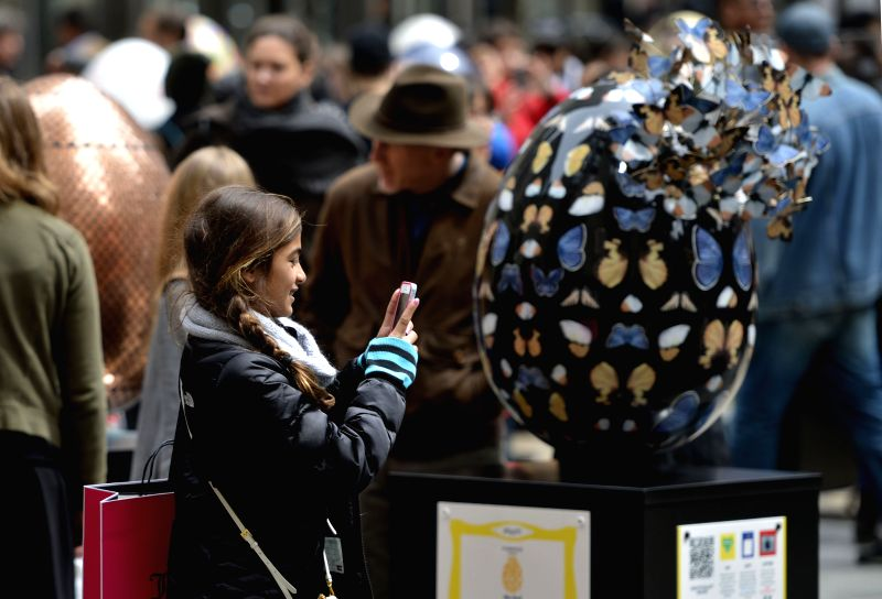 A girl takes photos of an egg sculpture at the Rockefeller Center in the New York City, April 18, 2014. More than 260 Easter eggs, designed by well-known artists .
