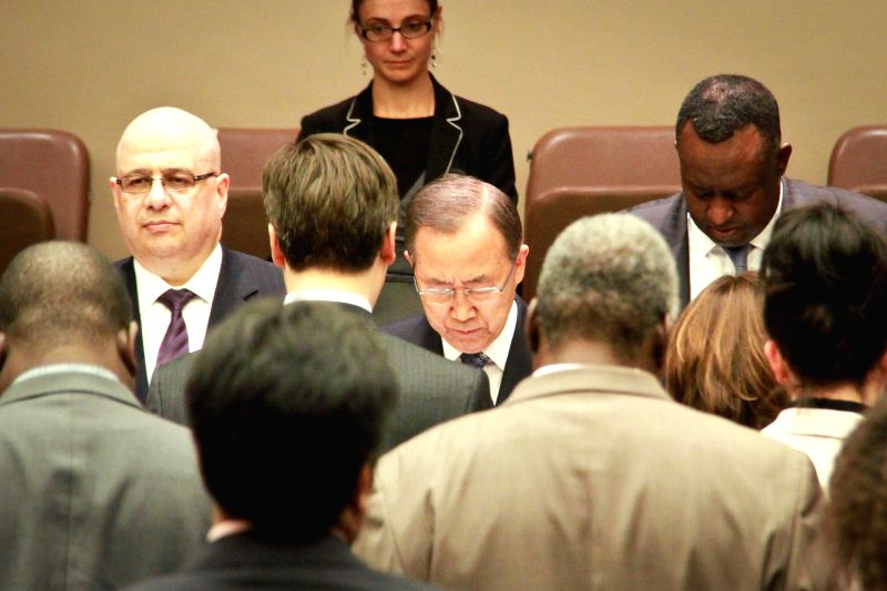 UN Secretary-General Ban Ki-moon (C) and other participants observe a minute of silence during an event in commemoration of the Rwanda Genocide, at the UN ...