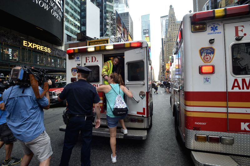 Police officers transfer injured people near the site where two buses collided at Times Square, New York City, the United States, on Aug. 5, 2014. Two sightseeing