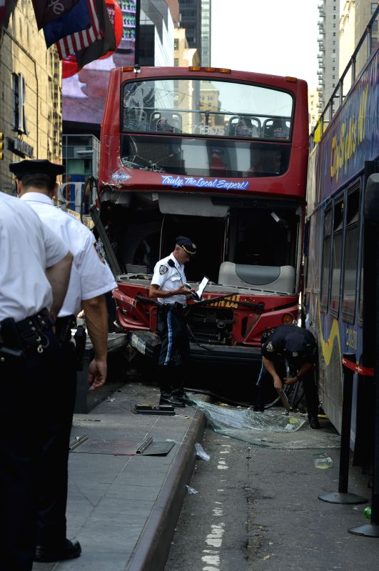 Police officers inspect the site where two buses collided at Times Square, New York City, the United States, on Aug. 5, 2014. Two sightseeing buses crashed at the .
