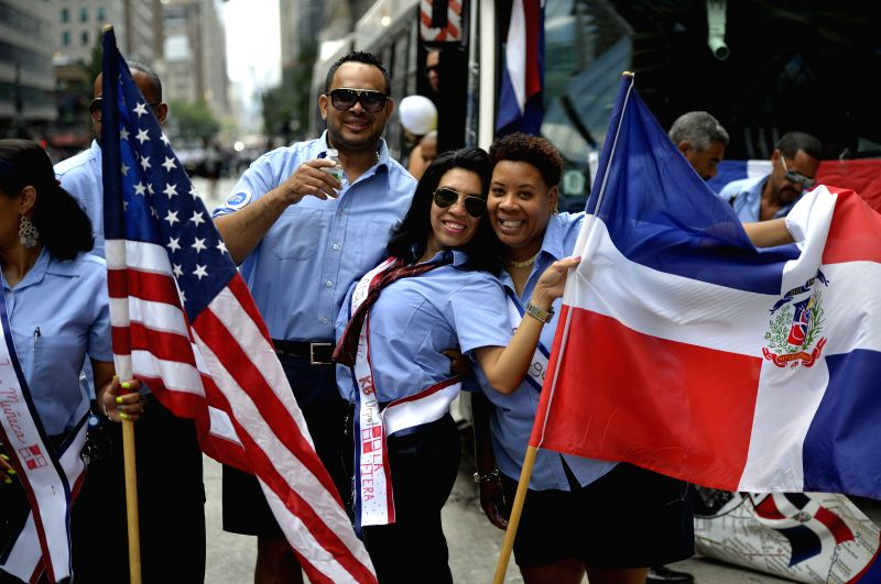 People pose for photos during the Dominican Day Parade in New York, the United States, Aug. 10, 2014. Dominican Day is a festive occasion celebrating Dominican ...