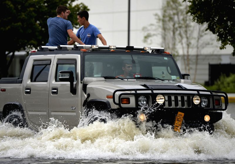 A car drives on a waterlogged road following heavy rains and flash flooding in Bay Shore in New York, the United States, on Aug. 13, 2014. A rain storm saturated .