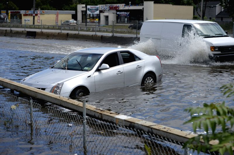 A car is abandoned on a flooded road following heavy rains and flash flooding in Bay Shore in New York, the United States, on Aug. 13, 2014. A rain storm ...