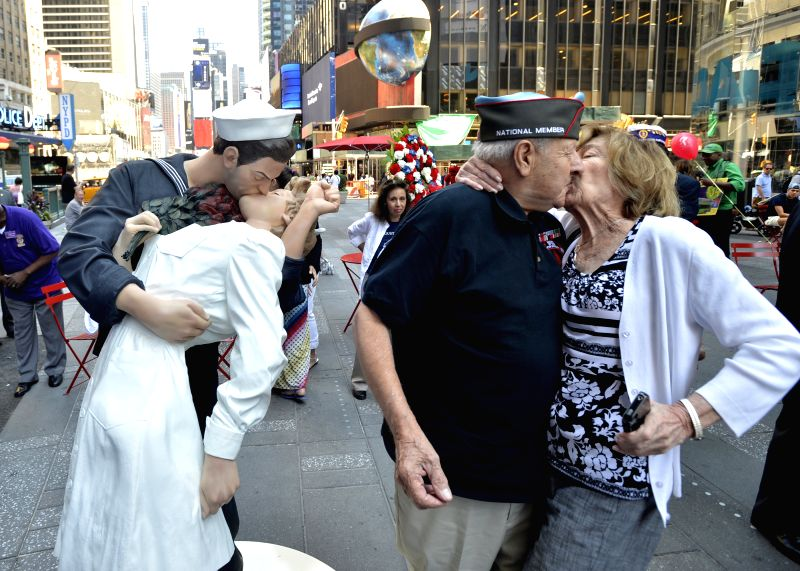 "A veteran kisses his wife during the unveiling ceremony of the ""Times Square Kiss"" statue in New York, the United States, on Aug. 14, 2014. A ..."