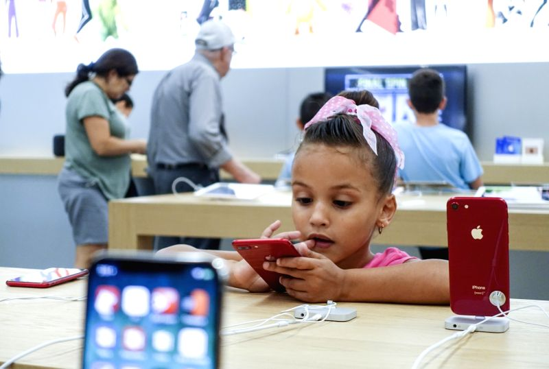 NEW YORK, Aug. 2, 2018 - A girl tries a product at an Apple store in New York, the United States, Aug. 2, 2018. U.S. tech giant Apple became the first American company that saw its market cap hit 1 ...