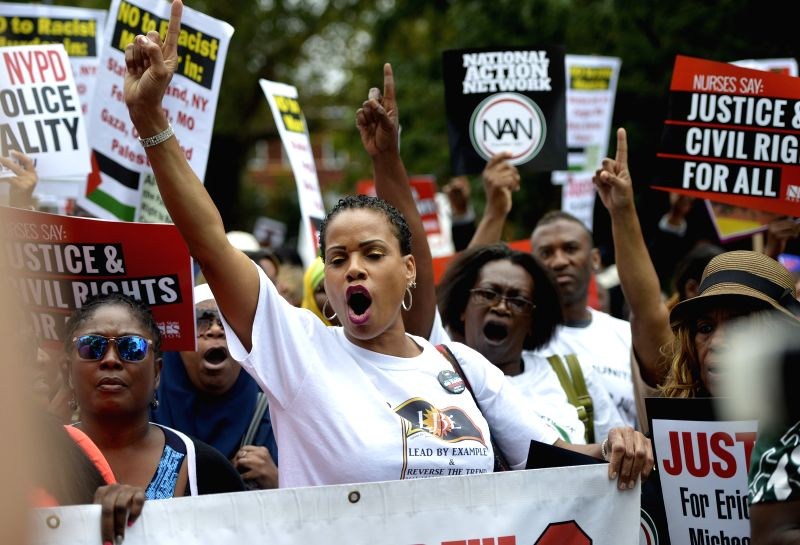 People hold placards and shout out to protest over police killing in New York's Staten Island, the Unites States, on Aug. 23, 2014. Thousands marched peacefully in