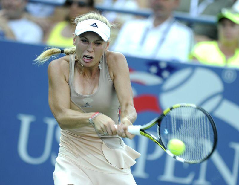 Caroline Wozniacki of Denmark returns the shuttle during the second round match of women's singles against Aliaksandra Sasnovich of Belarus at the 2014 U.S.Open in