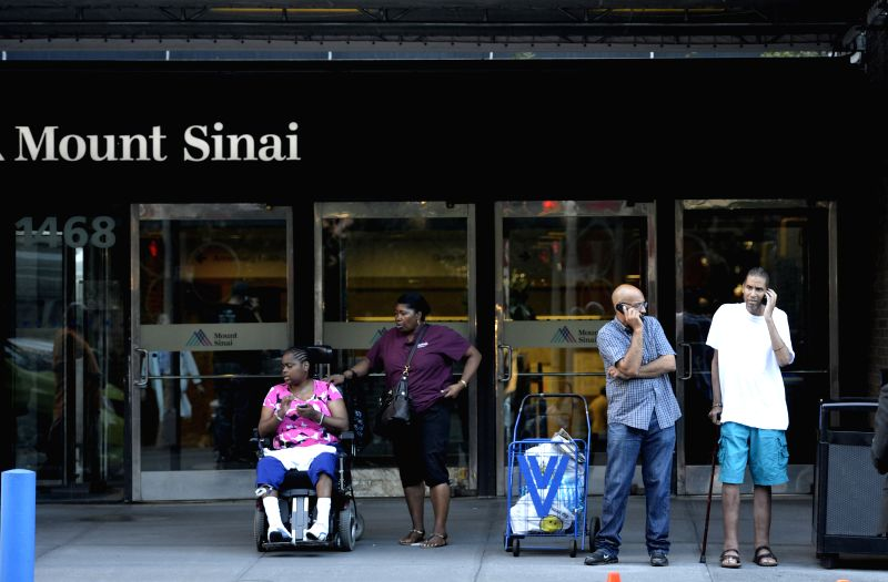 People are seen in front of Mount Sinai Hospital in New York, the United States, Aug. 4, 2014. Officials have announced that a male patient who recently traveled to