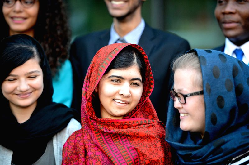 Education advocate Malala Yousafzai (C) poses for a picture with youths upon her arrival for a special event marking 500 days of action for the Millennium ...