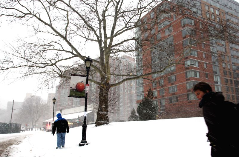 Pedestrians walk in snow on Roosevelt Island in New York, the United States, Jan. 26, 2015. New York State Governor Andrew Cuomo declared here Monday a state of ...