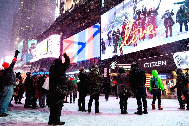 People watch screen in snow in Times Square in New York, the United States, Jan. 26, 2015. New York State Governor Andrew Cuomo declared here Monday a state of ...