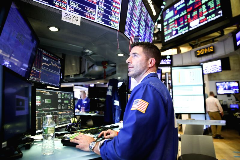 NEW YORK, July 13, 2018 - A trader works at the New York Stock Exchange in New York, the United States, on July 13, 2018. U.S. stocks closed higher on Friday. The Dow Jones Industrial Average rose ...