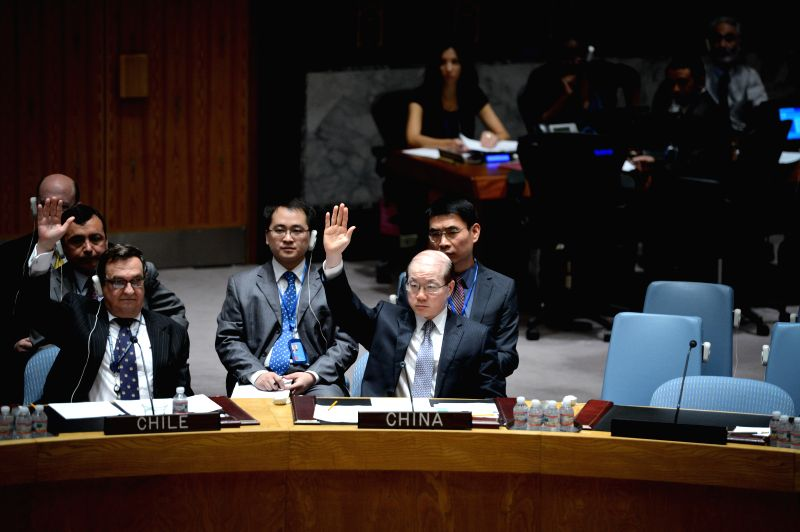 Permanent Representative to the United Nations Liu Jieyi (C) votes for a Security Council draft resolution regarding Syria, at the UN headquarters in New York, on .